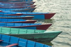 A empty old wooden blue red green boats on the water stand in a row stock photos