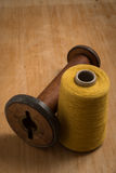 Empty Old Wooden Spool Beside Yellow Thread Royalty Free Stock Images
