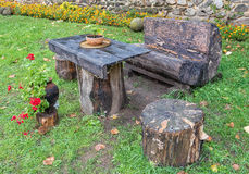 Empty old wooden table with chairs made of logs Royalty Free Stock Photos