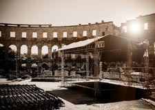 Empty open air stage in ancient theater. Empty open air stage at ancient roman amphitheater in Pula, Croatia. Low-key monochrome image Stock Image