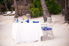 Empty open air table set for dinner on white beach Royalty Free Stock Image