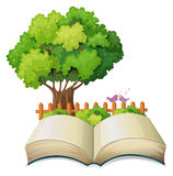An empty open book and a tree with a fence Stock Image
