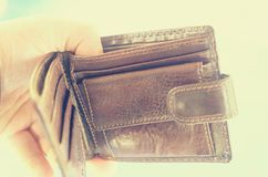 Empty open brown purse in one hand. Royalty Free Stock Image