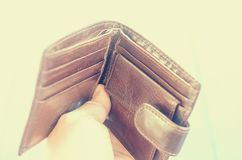 Empty open brown purse in one hand. Royalty Free Stock Photos