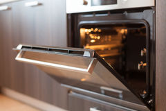 Empty open electric oven with hot air ventilation. New oven. Door is open and light is on. Stock Photo