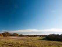 Empty open grass land farm land scene plain agriculture blue sky. Clear; essex; england; uk Royalty Free Stock Image