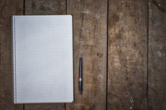 Empty open notebook with pen on brown wooden surface. Empty space on the right Royalty Free Stock Images
