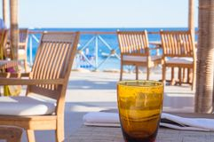 Empty orange glass on table at beach cafe stock photos