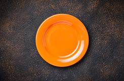 Empty plate on concrete table. Empty orange plate on concrete table royalty free stock images