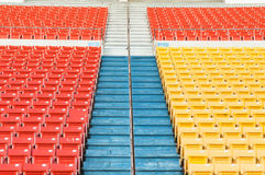 Empty orange and yellow seats at stadium Stock Photo
