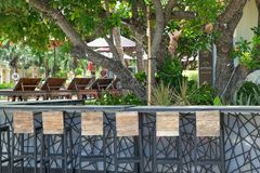 Empty outdoor bar counter with high black metal chairs in tropical resort background royalty free stock images