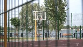Empty outdoor basketball court with two basketball hoop and green trees background. Shot in 4k resolution.  stock footage