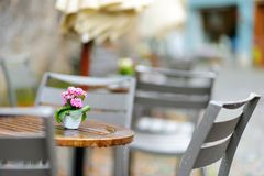 Empty outdoor cafe on beautiful rainy autumn day in Lindau, Germany. Empty chiars and tables under falling rain in autumn. Empty outdoor cafe on beautiful rainy Royalty Free Stock Photo