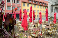 Empty outdoor cafe on beautiful rainy autumn day in Lindau, Germany. Empty chiars and tables under falling rain in autumn. Empty outdoor cafe on beautiful rainy Royalty Free Stock Photography