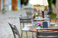 Empty outdoor cafe on beautiful rainy autumn day in Lindau, Germany. Empty chiars and tables under falling rain in autumn. Empty outdoor cafe on beautiful rainy Stock Photos