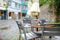 Empty outdoor cafe on beautiful rainy autumn day in Lindau, Germany. Empty chiars and tables under falling rain in autumn. Empty outdoor cafe on beautiful rainy Royalty Free Stock Images
