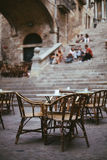 Empty outdoor cafe in old town. Street restaurant. Menu of Mediterranean tasty food. Evening daytime. Time for evening meal.  People sitting on the steps and Stock Photo