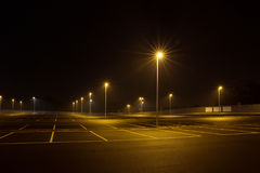 Empty outdoor car park at night shined with street lamps. Royalty Free Stock Image
