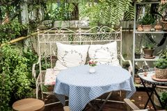 Empty outdoor patio table and chair decoration in garden. Vintage effect filter Royalty Free Stock Image