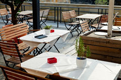 Empty outdoor tables of waterfront restaurant Stock Photos