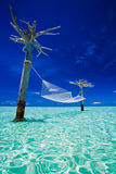 Empty over-water hammock in the middle of lagoon stock image