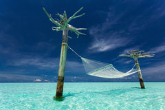 Empty over-water hammock in the middle of tropical lagoon Royalty Free Stock Image