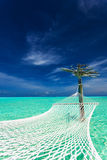 Empty over-water hammock in the tropical lagoon in Maldives Royalty Free Stock Image