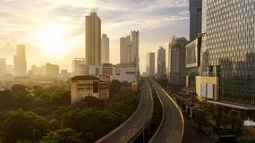 Empty overpass with skyscrapers at sunset time. JAKARTA - Indonesia. May 21, 2018: Aerial view of empty overpass with skyscrapers at sunset time Royalty Free Stock Images