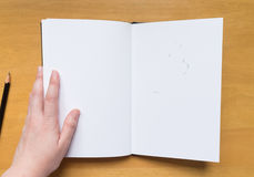 Empty page in sketchbook with hand and rubber leftovers Royalty Free Stock Photos