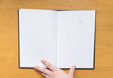 Empty page in sketchbook with hand and rubber leftovers Royalty Free Stock Image