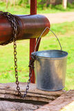 Empty pail, chain and well pulley Royalty Free Stock Images