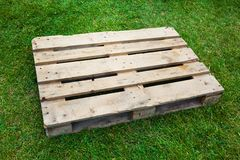 Empty pallet on green grass Royalty Free Stock Photo