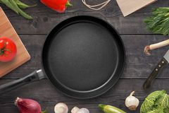 Empty pan on a kitchen table surrounded by vegetarian cuisine ingredients.  Royalty Free Stock Photos