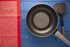 Empty pan with spade of frying pan and red tablecloth on blue wo Royalty Free Stock Photography