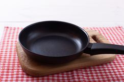 Empty pan on wooden deck table with tablecloth Royalty Free Stock Images