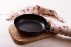 Empty pan on wooden deck table with tablecloth Stock Images