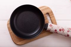 Empty pan on wooden deck table with tablecloth Royalty Free Stock Photo