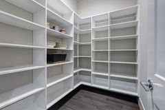 Empty pantry interior with white shelves and dark floor. Empty pantry interior with white shelves and dark wood floor. Northwest, USA Stock Photos