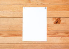 Empty paper ad loose leaves on a wooden wall. Attached metal but Royalty Free Stock Photos