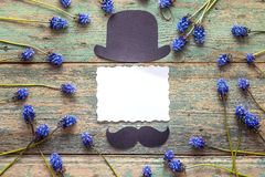 Empty paper card with cardboard hat and mustache and blue flower Royalty Free Stock Photos