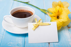 Empty paper card, coffee and yellow flower on blue colored woode Royalty Free Stock Image