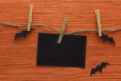 Empty paper card is hanging on clothespins with decorative bats on a orange wooden background. Halloween background. Royalty Free Stock Photography
