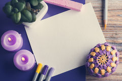 Empty paper and colorful pencils. Top view of empty paper and colorful pencils on wooden table, purple candles, paperweight. Toned vintage Royalty Free Stock Photos
