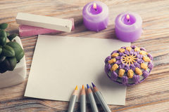 Empty paper and colorful pencils. Top view of empty paper and colorful pencils on wooden table, purple candles, paperweight. Toned vintage Stock Photography
