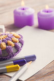 Empty paper and colorful pencils. On wooden table, purple candles, paperweight. Toned vintage Royalty Free Stock Photography