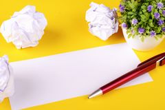 Empty paper with crumpled paper balls. On yellow background. Copy space. Brainstorming concept stock images