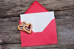 Empty paper in an envelope with heart cookies on wooden table Royalty Free Stock Image