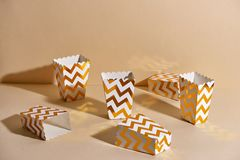 Empty paper golden Christmas cups for winter holidays meetings w. Ith friends with New Year`s Christmas decor on a beige background royalty free stock photography