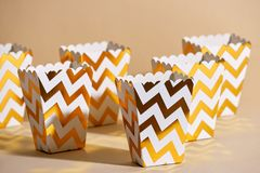 Empty paper golden Christmas cups for winter holidays meetings w. Ith friends with New Year`s Christmas decor on a beige background stock images