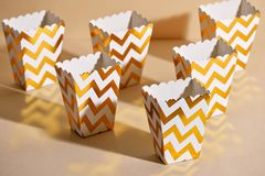 Empty paper golden Christmas cups for winter holidays meetings w. Ith friends with New Year `s Christmas decor on a beige background royalty free stock photography